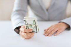 Fermez-vous des mains de femme tenant argent de dollar US Image stock