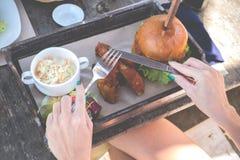Fermez-vous des mains de femme tenant la fourchette et le couteau sur l'hamburger délicieux Aliments de préparation rapide améric Image libre de droits
