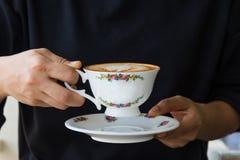 Fermez-vous des mains de femme tenant la tasse de vintage de café Image libre de droits