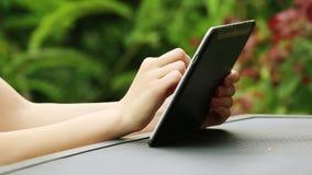 Fermez-vous des mains de femme utilisant la tablette dehors banque de vidéos