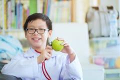 Fermez-vous des mains de garçon avec la pomme verte, le petit avenir mignon d de garçon photo libre de droits