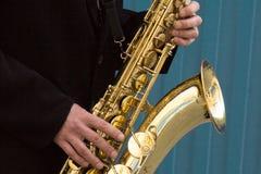 Fermez-vous des mains de joueur de saxophone de rue jouant l'instrument de musique de saxo d'alto au-dessus du fond bleu, plan ra photos stock