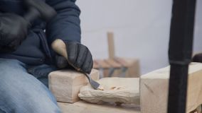 Fermez-vous des mains de l'artisan d?coupent avec une gouge dans les mains sur l'?tabli en menuiserie banque de vidéos