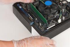 Fermez-vous des mains de l'homme avec des gants installant le mod de mémoire du Ram DDR4 Photo libre de droits