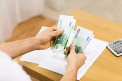 Fermez-vous des mains de l'homme comptant l'argent à la maison Image stock