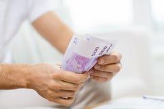 Fermez-vous des mains de l'homme comptant l'argent à la maison Photographie stock libre de droits