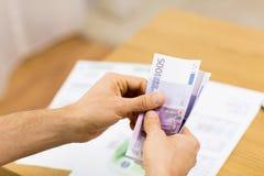 Fermez-vous des mains de l'homme comptant l'argent à la maison Image libre de droits