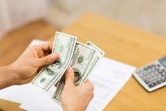 Fermez-vous des mains de l'homme comptant l'argent à la maison Photos libres de droits