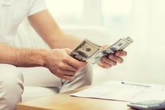 Fermez-vous des mains de l'homme comptant l'argent à la maison Photos stock