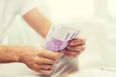 Fermez-vous des mains de l'homme comptant l'argent à la maison Photographie stock