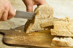 Fermez-vous des mains de l'homme coupant en tranches un pain de pain fait maison avec les graines de sésame sur une planche à déc images libres de droits