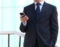 Fermez-vous des mains de l'homme d'affaires avec un téléphone portable Images libres de droits