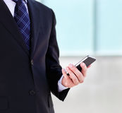 Fermez-vous des mains de l'homme d'affaires avec un téléphone portable Image stock