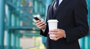 Fermez-vous des mains de l'homme d'affaires avec un téléphone portable et Photo stock