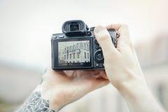 Fermez-vous des mains de l'homme tenant l'appareil-photo et faisant des photos du bâtiment moderne image stock