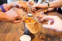 Fermez-vous des mains de personnes prenant des boules de fromage Image stock
