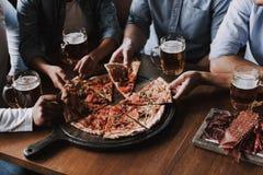 Fermez-vous des mains de personnes prenant des tranches de pizza photos libres de droits