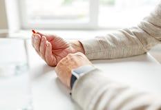 Fermez-vous des mains de vieil homme avec la pilule Photographie stock