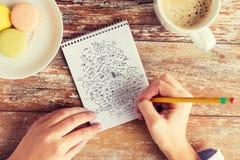 Fermez-vous des mains dessinant le plan au carnet Image stock