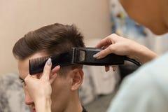 Fermez-vous des mains du jeune coiffeur faisant la coupe de cheveux à l'homme attirant dans le raseur-coiffeur photographie stock libre de droits