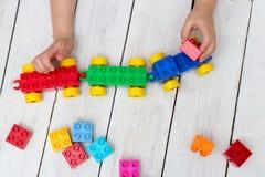 Fermez-vous des mains du ` s d'enfant jouant avec les briques en plastique colorées a photo stock