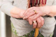 Fermez-vous des mains du ` s de dame âgée sur la poignée de parapluie Images stock
