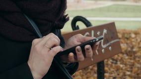 Fermez-vous des mains du ` s de femme utilisant Smartphone se reposant sur le banc en parc Beau service de mini-messages européen banque de vidéos