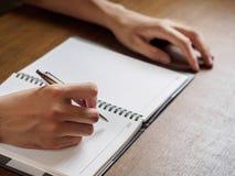 Fermez-vous des mains du ` s de l'homme écrivant dans le carnet placé sur le DES en bois image stock