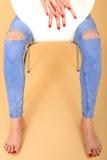 Fermez-vous des mains et des pieds de jeans modèles de Sitting In Ripped Photo libre de droits