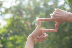 Fermez-vous des mains faisant le geste de cadre Fermez-vous des mains de femme Photos libres de droits