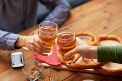Fermez-vous des mains faisant tinter la bière à la barre ou au bar Photographie stock libre de droits
