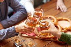 Fermez-vous des mains faisant tinter la bière à la barre ou au bar Photos libres de droits