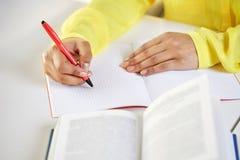 Fermez-vous des mains femelles écrivant au carnet Images stock