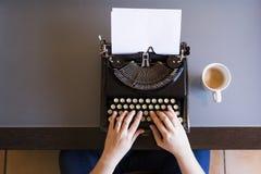 Fermez-vous des mains femelles dactylographiant sur la rétro machine à écrire Tasse de coff photos stock