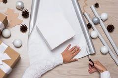 Fermez-vous des mains femelles emballant des cadeaux de Noël au-dessus d'étiquette en bois image stock