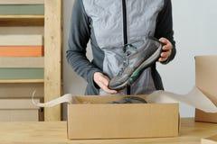Fermez-vous des mains femelles emballant les marchandises sportives Chaussures de sports Images libres de droits