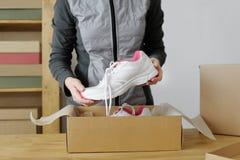 Fermez-vous des mains femelles emballant les marchandises sportives Chaussures de sports Photo libre de droits