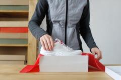 Fermez-vous des mains femelles emballant les marchandises sportives Chaussures de sports Images stock