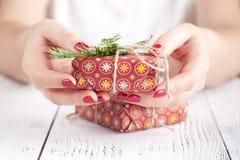 Fermez-vous des mains femelles jugeant un petit cadeau de Noël enveloppé avec la ficelle Petit cadeau dans les mains d'une femme  Photographie stock