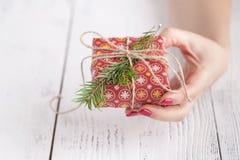 Fermez-vous des mains femelles jugeant un petit cadeau de Noël enveloppé avec la ficelle Petit cadeau dans les mains d'une femme  Photographie stock libre de droits