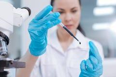 Fermez-vous des mains femelles tenant le compte-gouttes et le verre de médecine photographie stock libre de droits