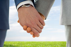 Fermez-vous des mains gaies masculines avec des anneaux de mariage dessus Images libres de droits