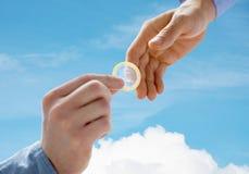 Fermez-vous des mains gaies masculines de couples donnant le préservatif Image libre de droits