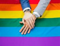 Fermez-vous des mains gaies masculines de couples sur le drapeau d'arc-en-ciel Photographie stock