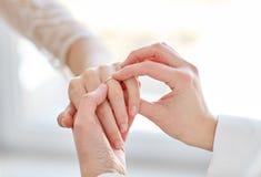 Fermez-vous des mains lesbiennes de couples avec l'anneau de mariage Photos stock