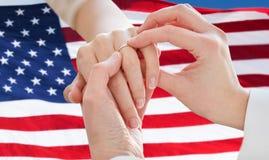 Fermez-vous des mains lesbiennes de couples avec l'anneau de mariage Image libre de droits