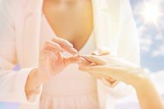 Fermez-vous des mains lesbiennes de couples avec l'anneau de mariage Photo stock