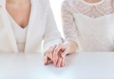 Fermez-vous des mains lesbiennes mariées heureuses de couples Images stock