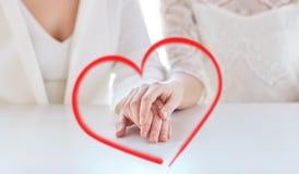 Fermez-vous des mains lesbiennes mariées heureuses de couples Photo libre de droits