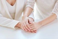 Fermez-vous des mains lesbiennes mariées heureuses de couples Image libre de droits